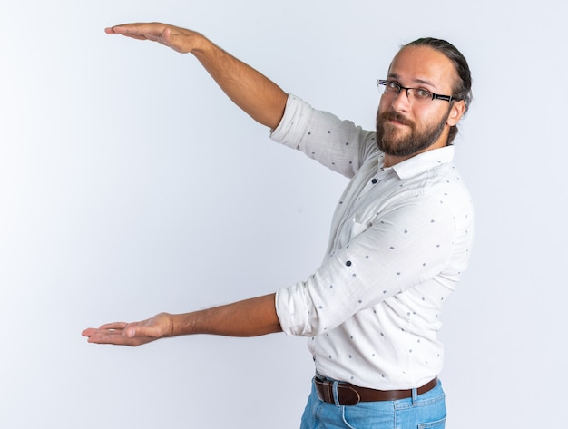 Piacere adulto bell'uomo con gli occhiali in piedi in vista di profilo facendo un gesto di taglia guardando la telecamera isolata sul muro bianco