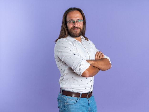 Pleased adult handsome man wearing glasses standing in profile view with closed posture looking at camera isolated on purple wall with copy space