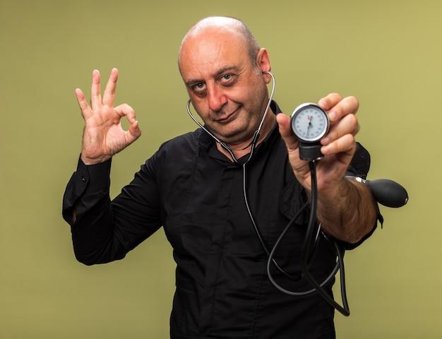 Piacere adulto malato uomo caucasico tenendo lo sfigmomanometro e gesticolando segno ok isolato sul verde oliva parete con spazio di copia