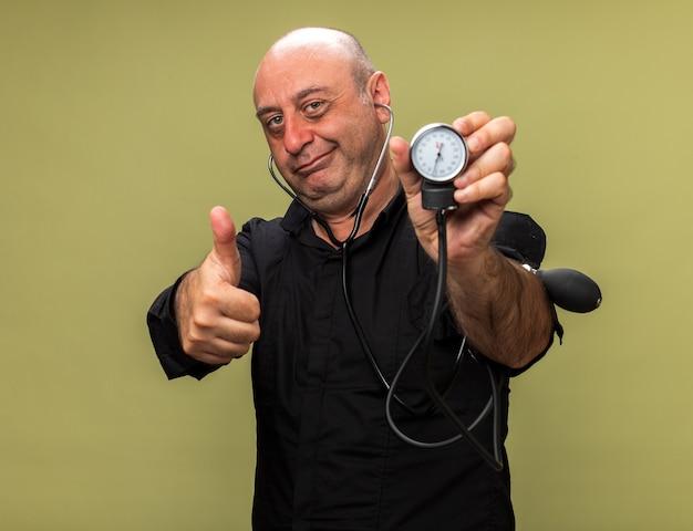 Compiaciuto adulto malato uomo caucasico tenendo lo sfigmomanometro e sfogliando isolato su verde oliva parete con spazio di copia