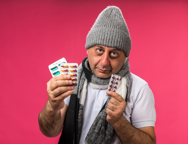 Pleased adult ill caucasian man with scarf around neck wearing winter hat holding different medicine packs isolated on pink wall with copy space