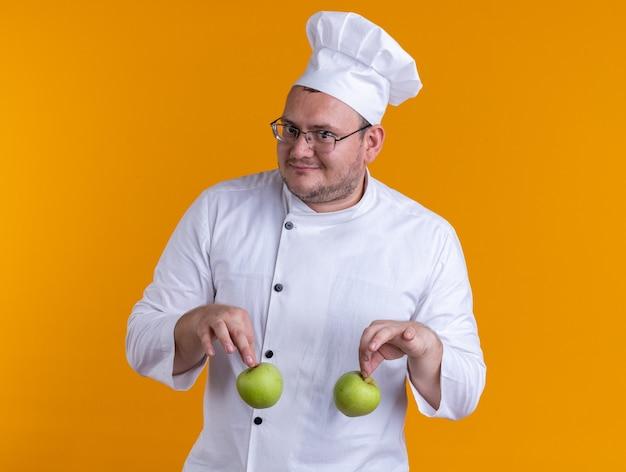 Довольный взрослый мужчина-повар в униформе шеф-повара и в очках держит яблоки, глядя в камеру, изолированную на оранжевом фоне