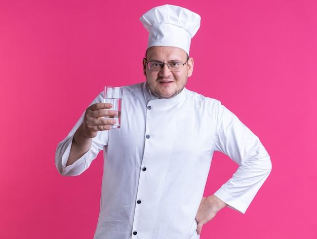 ピンクの壁で隔離された腰に手を保つシェフの制服と水のガラスを保持しているメガネを身に着けている大人の男性料理人を喜ばせる