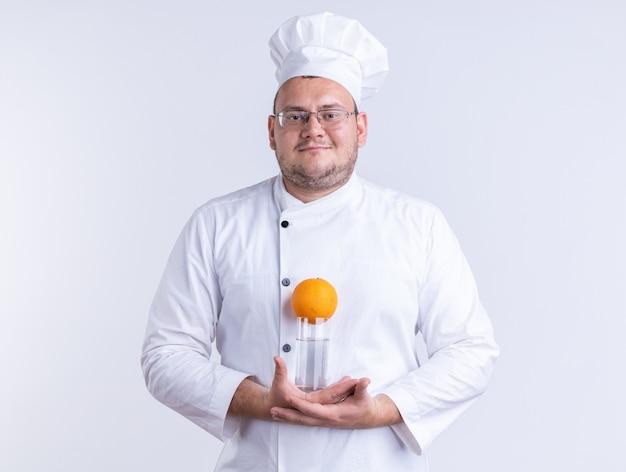 シェフの制服と白い壁に隔離された正面を見てオレンジ色の水のガラスを保持しているメガネを身に着けている大人の男性料理人を喜ばせる