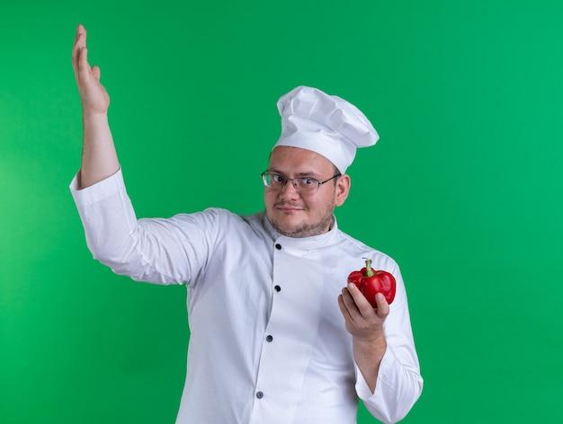 シェフの制服を着て、緑の壁に隔離された手を上げて側面を見て唐辛子を保持しているメガネを身に着けている大人の男性料理人を喜ばせる