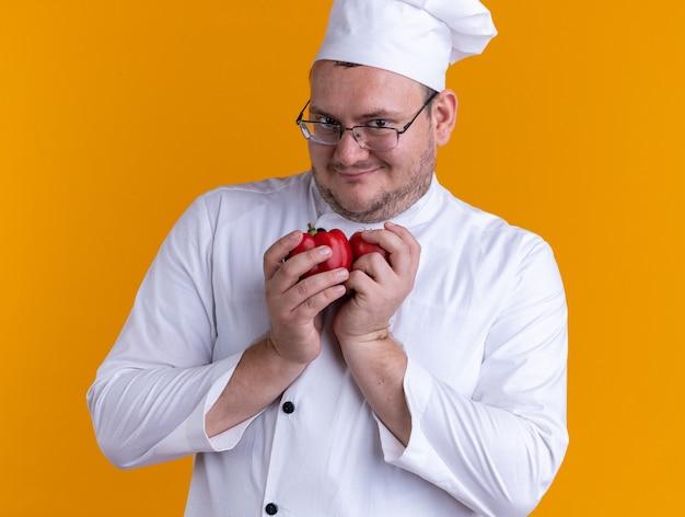 オレンジ色の壁に隔離された正面を見てシェフの制服とコショウを保持しているメガネを身に着けている大人の男性料理人を喜ばせる