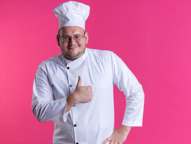 ピンクの壁に隔離された親指を上に見せて正面を見て腰に手を保ちながらシェフの制服と眼鏡を身に着けている大人の男性料理人を喜ばせる