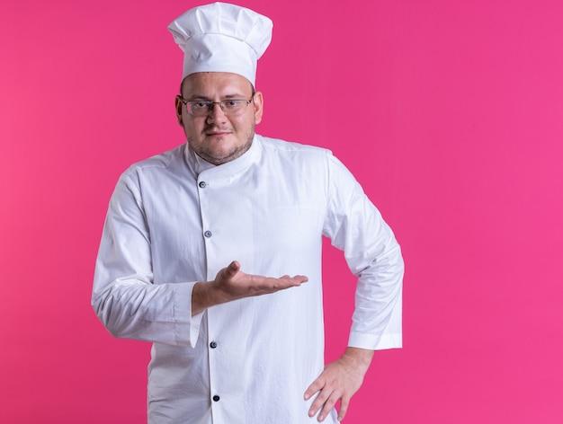 コピースペースのあるピンクの壁で隔離された正面を見て空の手を示して腰に手を保ち、シェフの制服と眼鏡を身に着けている大人の男性料理人を喜ばせます