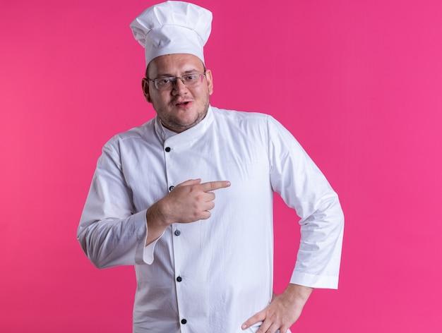ピンクの壁で隔離された側を指している腰に手を保ちながら正面を見てシェフの制服と眼鏡を身に着けている大人の男性料理人を喜ばせる