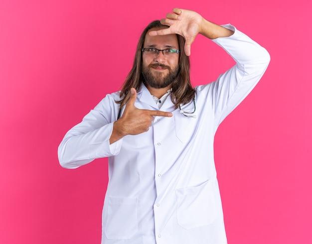 Felice maschio adulto medico che indossa accappatoio medico e stetoscopio con gli occhiali guardando la telecamera facendo il gesto del telaio isolato sulla parete rosa