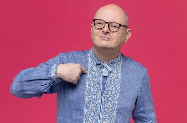 Uomo adulto contento in camicia blu con gli occhiali che punta a se stesso