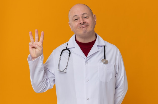 Pleased adult man in doctor uniform with stethoscope gesturing three with his fingers
