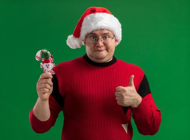 Довольный взрослый мужчина в очках и шляпе санта-клауса держит украшение из конфет, показывая большой палец вверх, глядя в камеру, изолированную на зеленом фоне