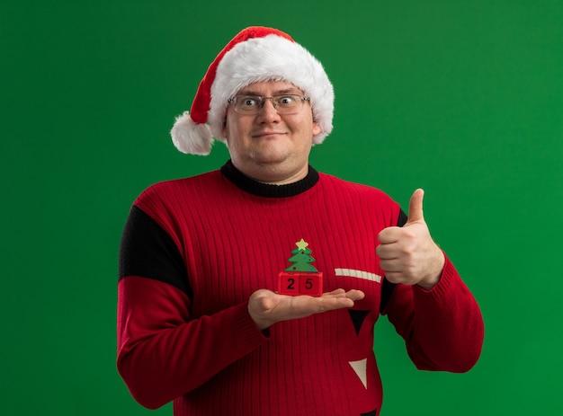 緑の背景に分離された親指を上に表示する側を見て日付とクリスマスツリーのおもちゃを保持しているメガネとサンタ帽子を身に着けている大人の男を喜ばせる
