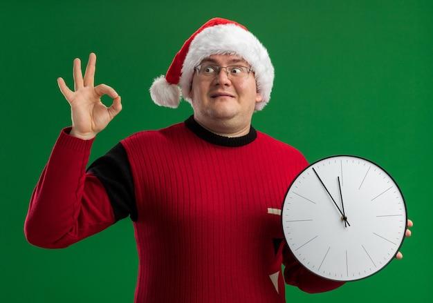 Uomo adulto soddisfatto con gli occhiali e cappello santa tenendo l'orologio guardando il lato facendo segno ok isolato su sfondo verde