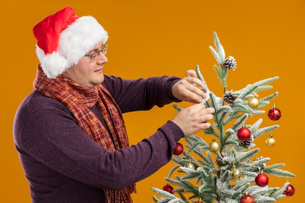 Lieto uomo adulto con gli occhiali e cappello da babbo natale con sciarpa intorno al collo in piedi in vista di profilo vicino all'albero di natale decorandolo isolato su sfondo arancione
