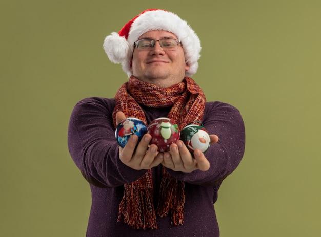 Felice uomo adulto che indossa occhiali e cappello da babbo natale con sciarpa intorno al collo che allunga le palline di natale isolate su una parete verde oliva