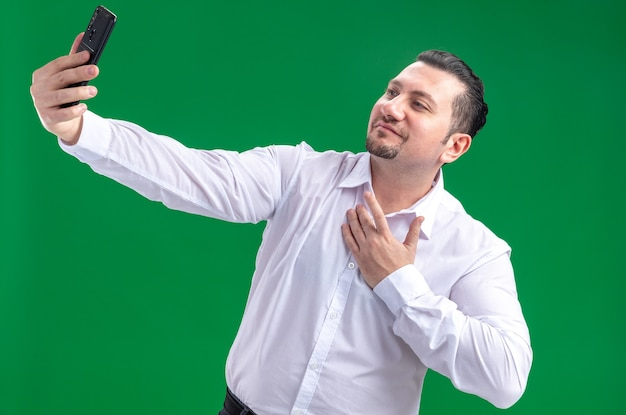 Pleased adult slavic businessman taking selfie on phone isolated on green wall with copy space