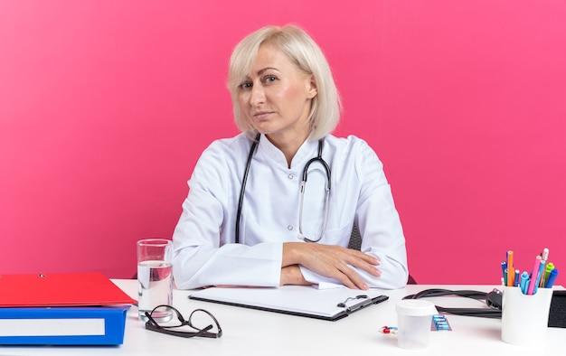 コピースペースでピンクの背景に分離されたカメラを見てオフィスツールと机に座って聴診器と医療ローブの大人のスラブ女性医師を喜ばせる