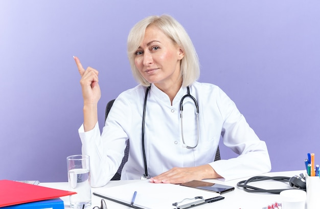 Pleased adult slavic female doctor in medical robe with stethoscope sitting at desk with office tools pointing up isolated on purple background with copy space