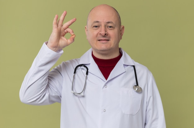 Pleased adult slavic man in doctor uniform with stethoscope gesturing ok sign looking