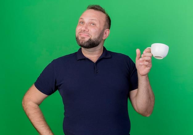 Piacere adulto slavo uomo che tiene la tazza guardando il lato isolato sulla parete verde