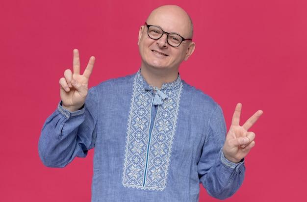 Довольный взрослый славянский мужчина в синей рубашке в оптических очках жестикулирует знак победы