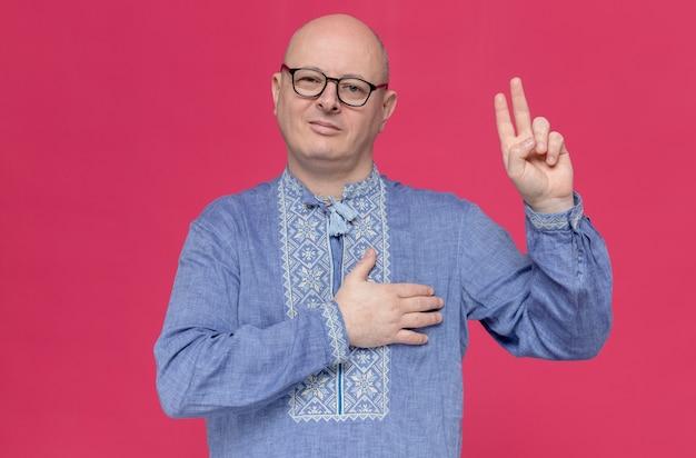 안경을 쓰고 가슴에 손을 대고 맹세하는 파란색 셔츠를 입은 기쁘게 성인 슬라브 남자