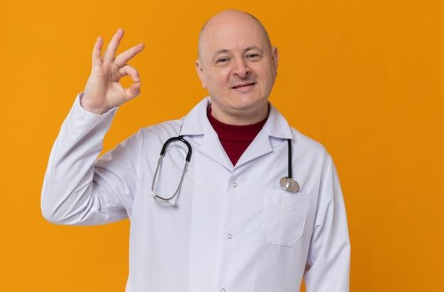 확인 표시를 몸짓으로 청진기와 의사 유니폼을 기쁘게 성인 슬라브 남자