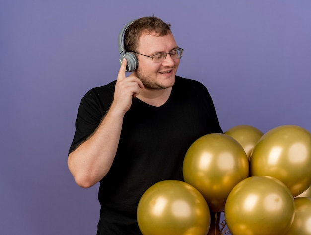Довольный взрослый славянский мужчина в оптических очках и в наушниках стоит с закрытыми глазами рядом с гелиевыми шарами