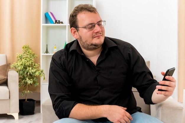 광학 안경에 만족 한 성인 슬라브 남자는 안락 의자에 앉아 거실 내부의 전화를보고 있습니다.