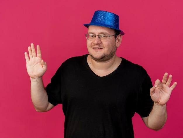 Довольный взрослый славянский мужчина в оптических очках в синей партийной шляпе жестикулирует знак рукой двумя руками