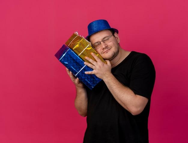 파란색 파티 모자를 쓰고 광학 안경을 쓴 만족스러운 성인 슬라브 남자가 선물 상자에 머리를 들고 있습니다.