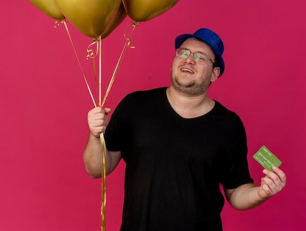 Довольный взрослый славянский мужчина в оптических очках в синей праздничной шляпе держит гелиевые шары и кредитную карту