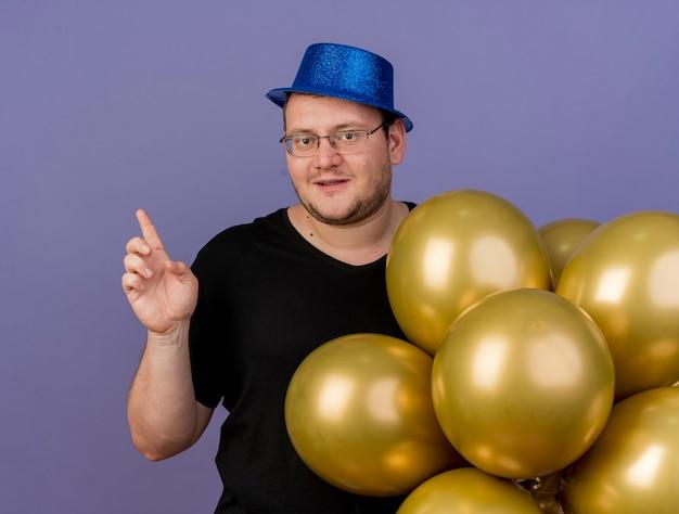 파란색 파티 모자를 쓰고 광학 안경에 만족 한 성인 슬라브 남자가 헬륨 풍선을 가리키는 스탠드