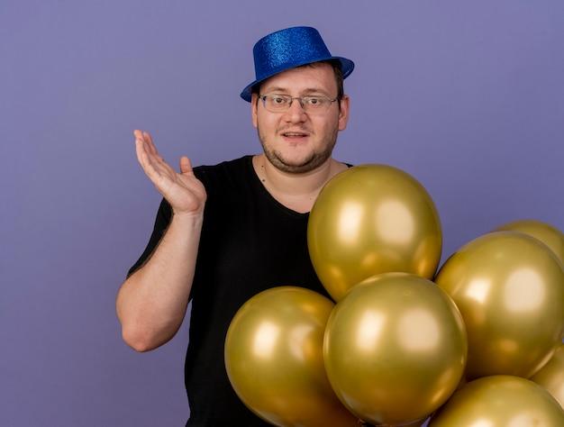 파란색 파티 모자를 쓰고 광학 안경에 기쁘게 성인 슬라브 남자가 헬륨 풍선 옆에 손을 들고 서 있습니다.
