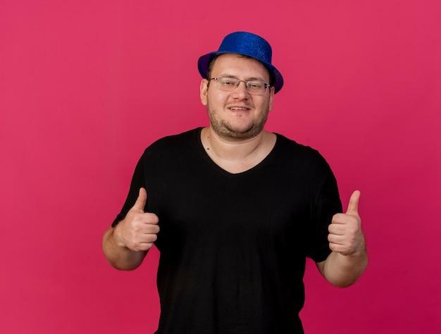 青いパーティー ハットを身に着けた光学メガネの大人のスラブ人が両手で親指を立てて喜ぶ