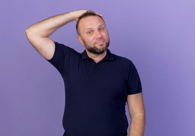 Uomo slavo adulto soddisfatto mantenendo la mano sulla testa isolata