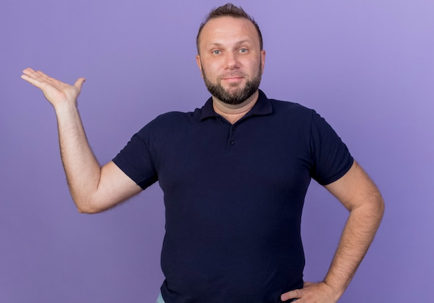 Довольный взрослый славянский мужчина смотрит, держась за талию и показывая пустую изолированную руку