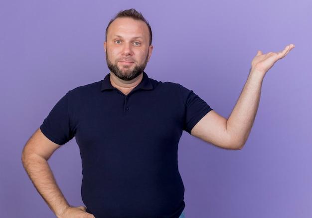 Uomo slavo adulto soddisfatto che osserva mantenendo la mano sulla vita e mostrando la mano vuota isolata