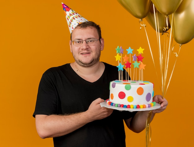 Pleased adult slavic man in optical glasses wearing birthday cap holds helium balloons and birthday cake looking at camera