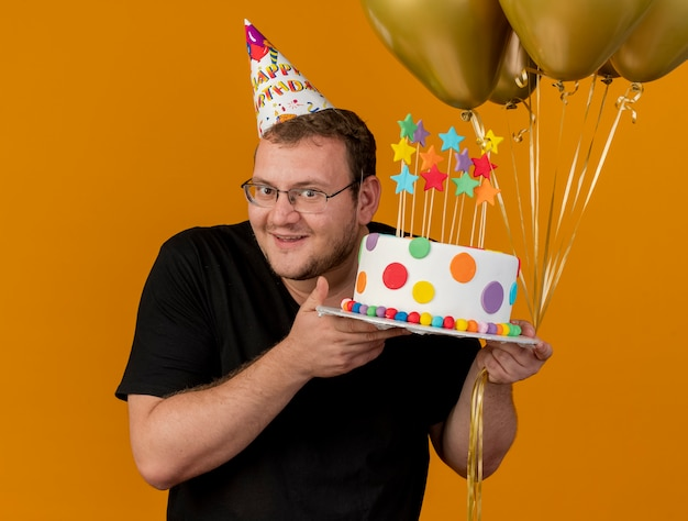 Pleased adult slavic man in optical glasses wearing birthday cap holds helium balloons and birthday cake