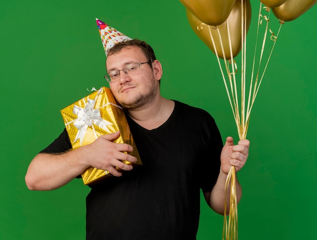 Pleased adult slavic man in optical glasses wearing birthday cap holds helium balloons and gift box