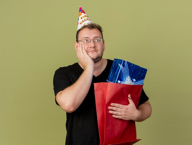 Pleased adult slavic man in optical glasses wearing birthday cap puts hand on face and holds gift box in paper shopping bag looking at side