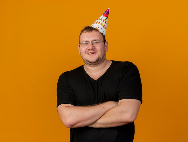 Pleased adult slavic man in optical glasses wearing birthday cap stands with crossed arms