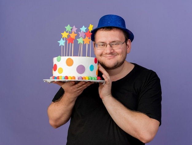 Pleased adult slavic man in optical glasses wearing blue party hat holds birthday cake