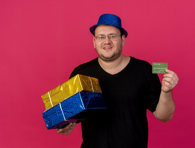 Pleased adult slavic man in optical glasses wearing blue party hat holds gift boxes and credit card