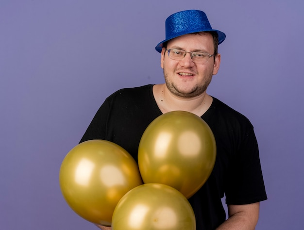 Pleased adult slavic man in optical glasses wearing blue party hat holds helium balloons