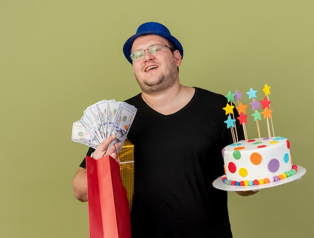 Pleased adult slavic man in optical glasses wearing blue party hat holds money gift box paper shopping bag and birthday cake