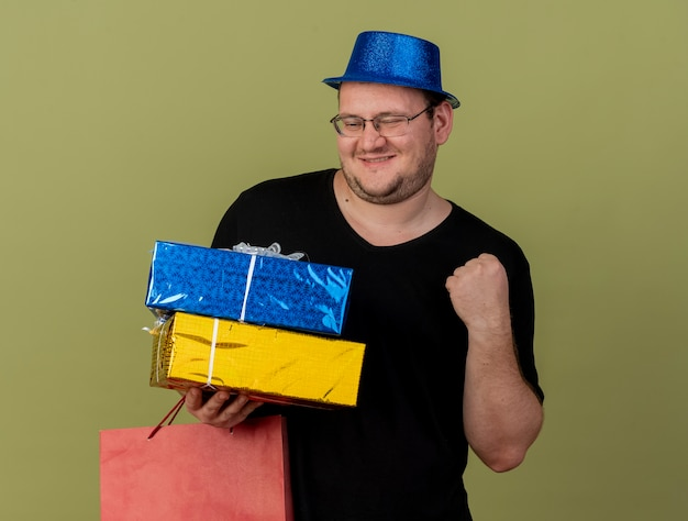Pleased adult slavic man in optical glasses wearing blue party hat keeps fist holds gift boxes and paper shopping bag